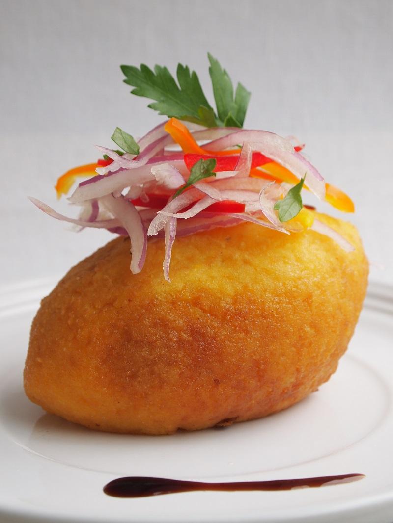 Stuffed potato accompanied by Creole sauce.